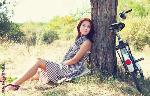 Beautiful girl sitting near bike and tree at rest in forest. Pho