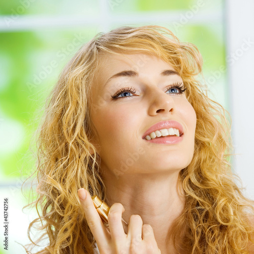 Smiling young woman with perfum bottle