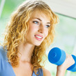 Young happy smiling woman with dumbbell, indoors