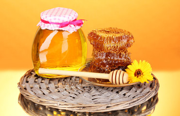 Jar of honey and honeycomb on orange background