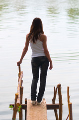 Lonely teenage girl standing on the edge of the river dock