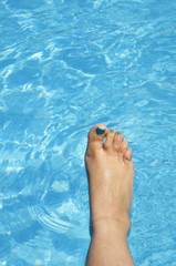female foot with blue nails in the pool