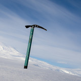 Ice axe with snow-capped mountain in the background