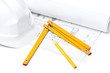 White hard hat, foot ruler and pencil on the druft, isolated