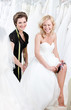 Laughing future bride in wedding gown puts the garter