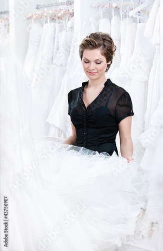 Shop assistant wants to select a proper dress for the client