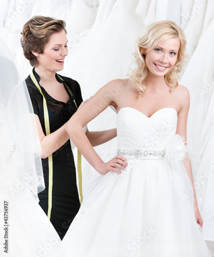 Seamstress adjusts the dress of the bride