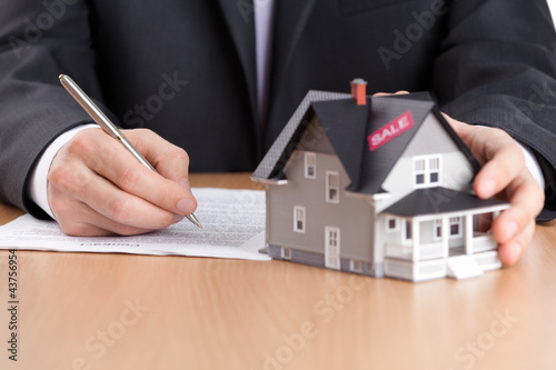 Businessman signs contract behind house architectural model