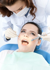 Dentist's assistant checks up the dentes of the patient