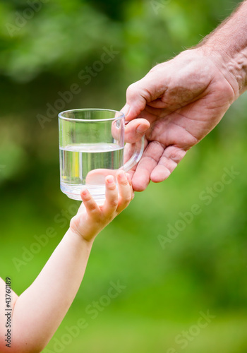Little girl taking a glass of water from grandpa