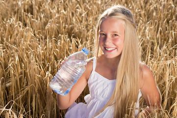 Blondes Mädchen trinkt Wasser im Getreidefeld