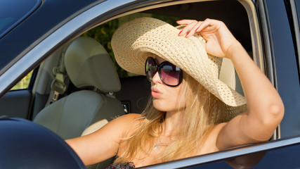 Beautiful woman driver in straw hat