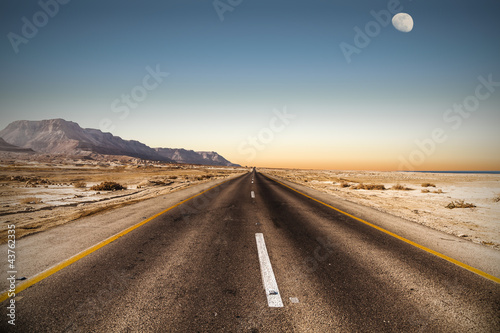 road in desert under the moon