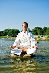 Man in kimono meditating on the rock in the sea