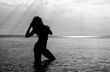 Black and white photo: Silhouette of woman in the sea