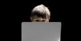 Junge sitzt vor Notebook
