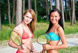 Two girls posing with badminton rackets on the beach