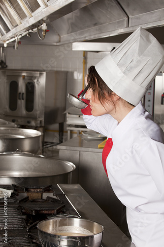 female chef at kitchen taste soup