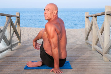 Man practising Yoga at the beach