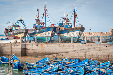 Blue fishing boats and ships in harbor