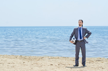 Businessman with football on beach