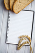blank notebook with bread and wheat