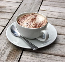 Cup of Cappuccino on wooden slat table