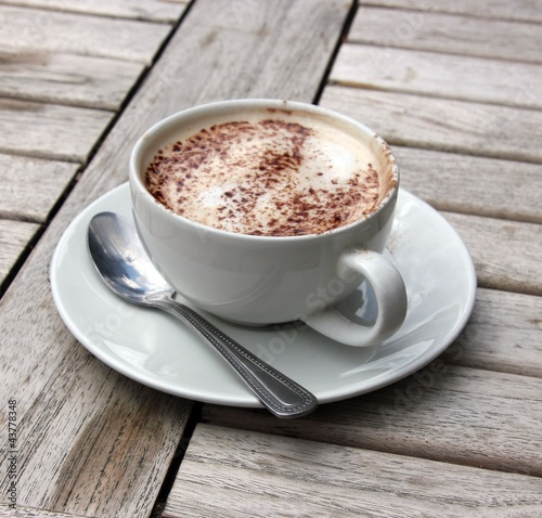 Aluminium Cafe Cup of Cappuccino on wooden slat table