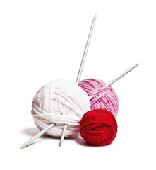 a group of multi-colored balls of yarn and knitting needles