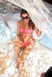 Beautiful young woman lying on sun lounger