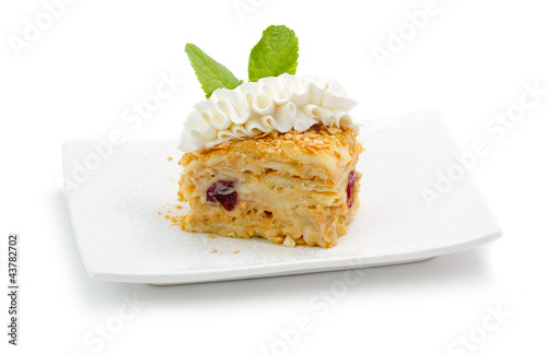 Portion of delicious pastry with cream and cherry isolated