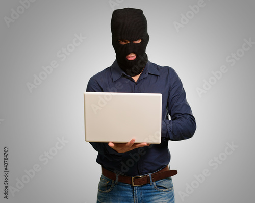 young male thief holding laptop
