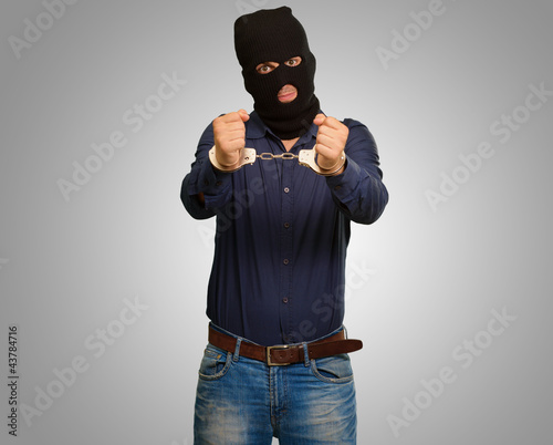angry criminal man locked in handcuffs