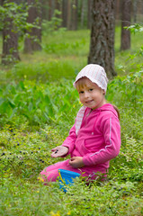 The little girl gathers bilberry in the wood