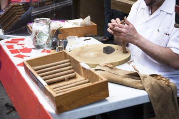 Man hand rolling cigars on the street