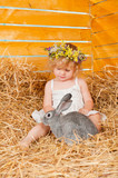 Beautiful little girl with a rabbit lying on the hay