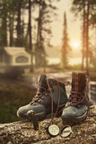 Hiking boots with compass at campsite poster