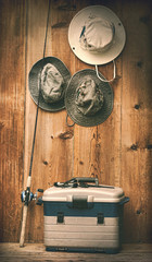 Hats hanging on wall with fishing equipment