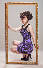 Beautiful girl posing in a violet dress, stilettos and frame
