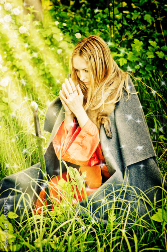 young girl on her knees praying in woods