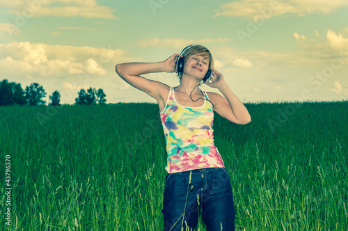 young woman with headphones on the field