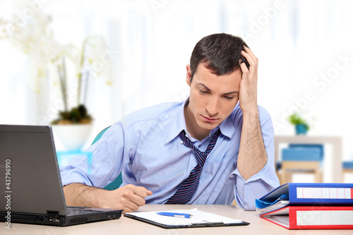 Young desperate businessman in his office looking down