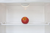 Open empty white refrigerator with an apple diet concept