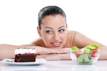 woman choosing between healthy food and tasty cakes