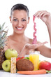 Young woman with fresh fruit and tape measure