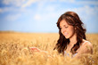 Smiling woman in golden wheat
