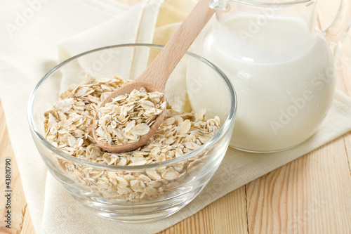Oat flaks on a glass bowl and jug of milk