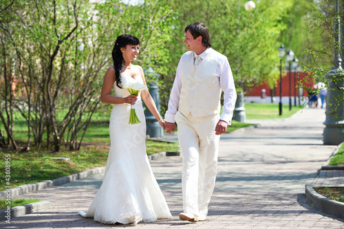 Happy groom and happy bride walking in park