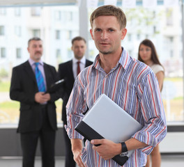 young business executive with his team in the background