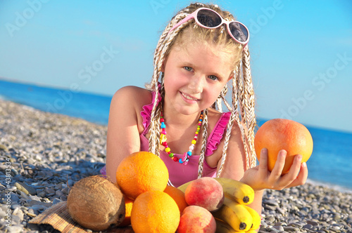 Happy child with tropical fruit on the beach